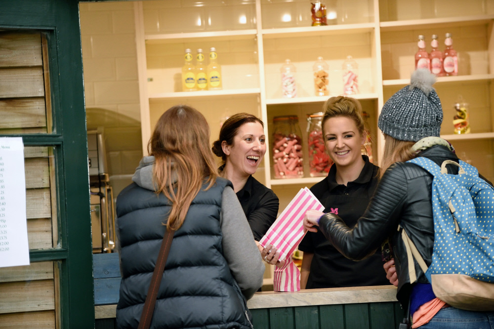 Two customers buying sweets from two National Trust members of staff