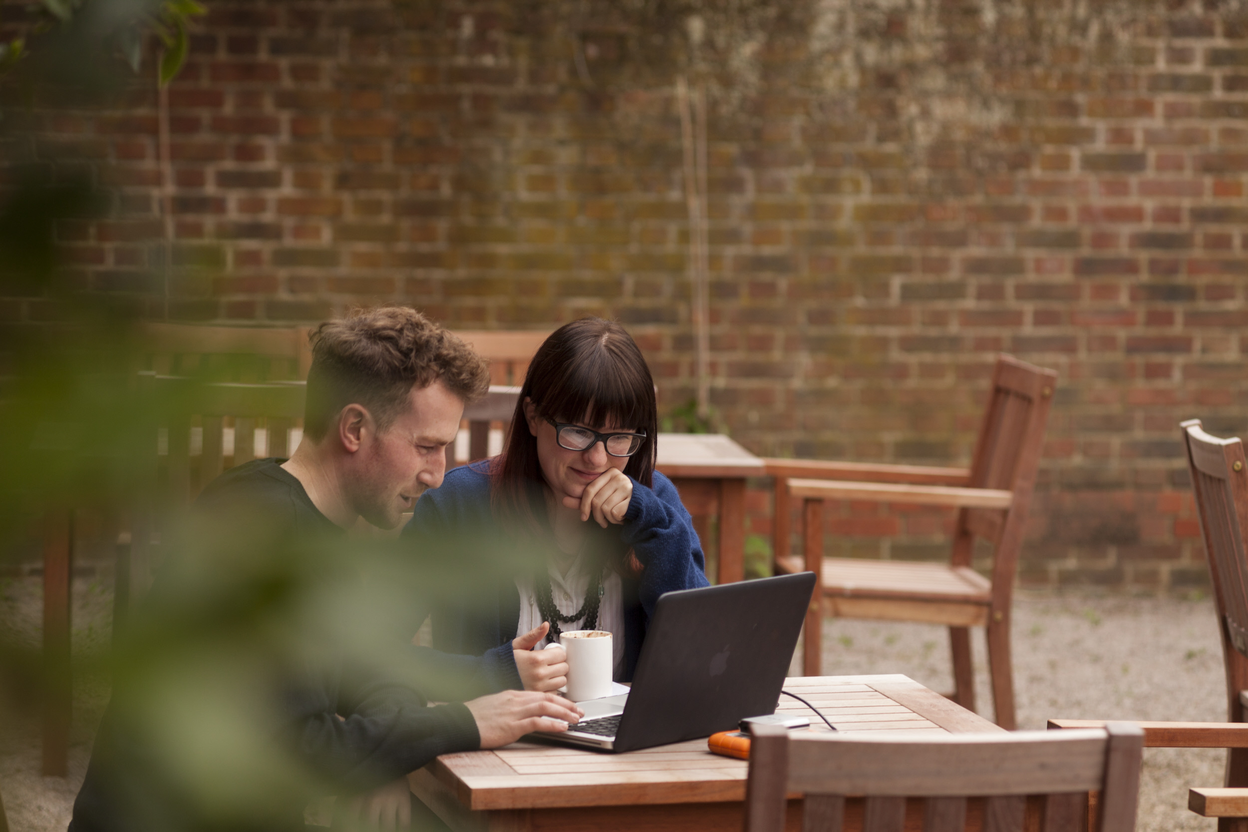 National Trust employees working outside with a laptop and coffee